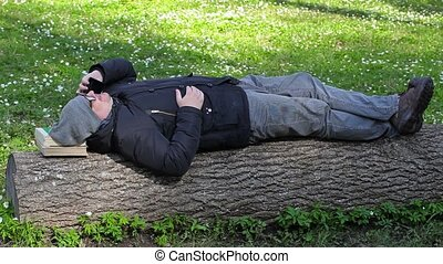 Man resting in meadow in the park and talking on smart phone