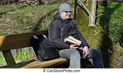 Man with two books in the park on bench