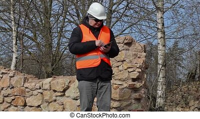 Building inspector using tablet PC at the ruins of old...