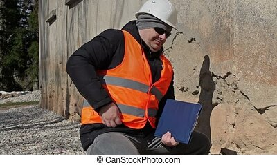 Building inspector talking on cell phone near old wall