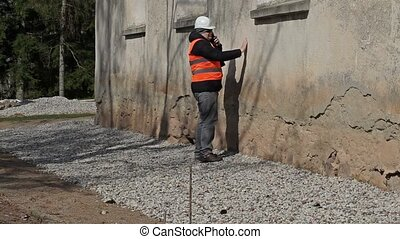 Building inspector checking old wall