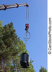 Crane hook lifts up the power transformer against the green...
