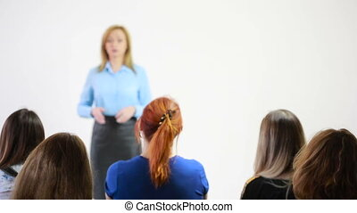 Beautiful business woman is speaking on conference. students...