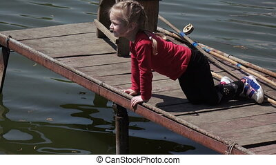 Little girl on riverside - In nature near river pier playing...