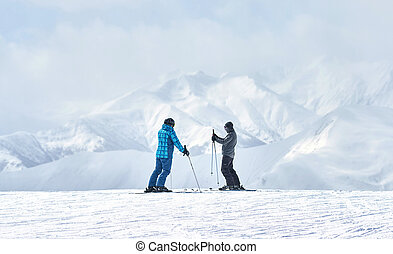 two skiers talking about something alone on a background of...