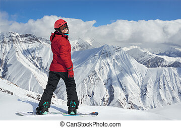 snowboarder in a red jacket on the edge of cliff -...