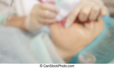 professional tattooist making permanent make up lips tattoo...