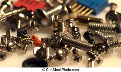 Screws and electronic components - Macro view of a spinning...