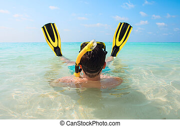 Man, relaxing in yellow black flippers fins and mask. - Man,...