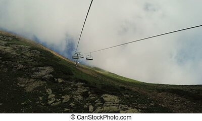 Lifts in mountains in summer fog - Shooting clouds and...