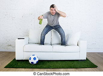 football fan watching tv match on sofa with grass pitch carpet in stress