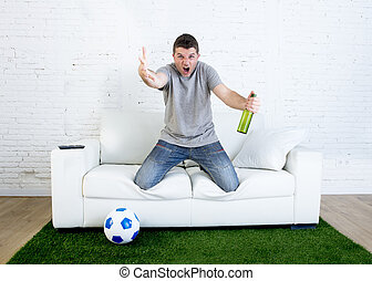 angry football fanatic fan watching game on television holding beer gesturing upset and crazy angry complaining