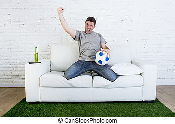 football fan watching tv match on sofa with grass pitch...