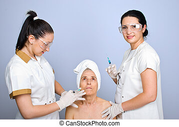 Doctor inject botox to senior cheek woman - Doctor inject...