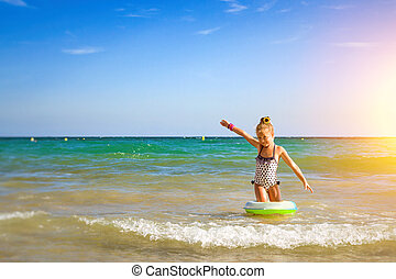 Cute girl in swimsuit bathes on waves in sea. Sunny...