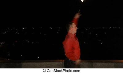Fire show in the dark - Men twist fiery circles on a fire...