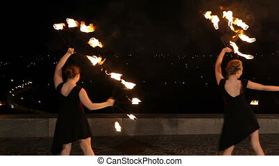 Fire show in the dark. - Women artists twist fiery circles...