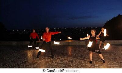 Fire show in the dark - Men and women artists twist fiery...
