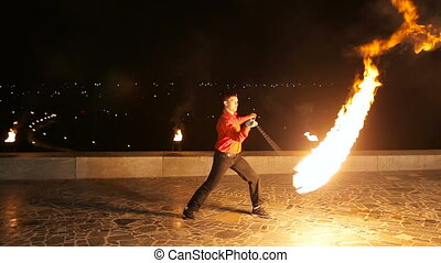 Fire show in the dark - Artist man rotates the fireballMan...
