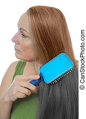 Gray to brown hair dye - Woman combs her hair gray to brown...