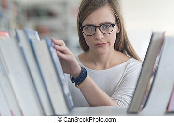portrait of famale student selecting book to read in library...