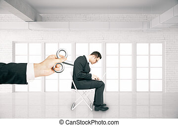 Man with wind-up key - Hand activating businessman with a...