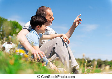 Senior male grandparent is teaching the boy - Mature...