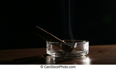 Smoking cigar in an ashtray.