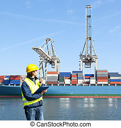 Docker using his radio at a large container terminal