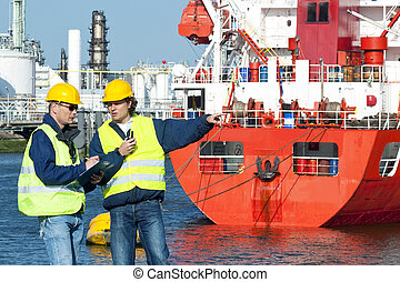 Dock workers - Two dockers at work, wearing safety vests...