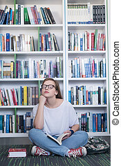 female student reading book in library - smart looking...