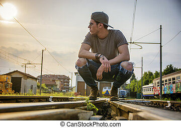 Attractive young man sitting on railroad, wearing grey...