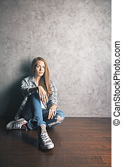 Girl sitting on wooden floor - Front view of attractive...