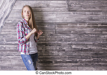 Girl against wooden wall - Thoughtful casually dressed...