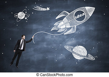 Startup concept with businessman holding onto abstract space...