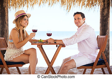 Honeymooners drinking wine at the beach