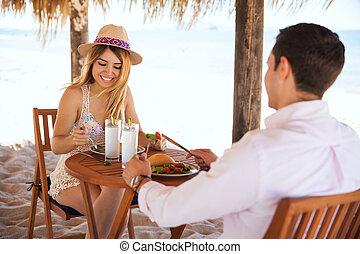 Honeymooners having lunch at the beach