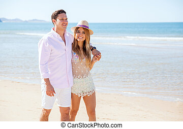 Pretty girl and her boyfriend walking at the beach -...