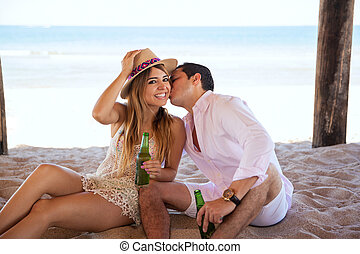 Guy kissing his girlfriend on her cheek - Young man giving a...