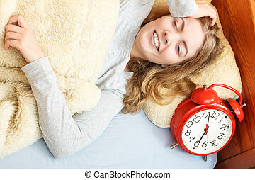 Woman waking up turning off alarm clock in morning - Happy...