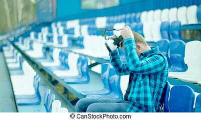 Man sitting on the tribune and putting on VR glasses - Young...