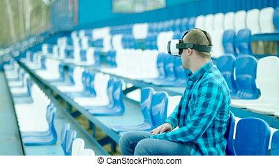 Upset guy in VR glasses sitting on the tribune - Guy in...