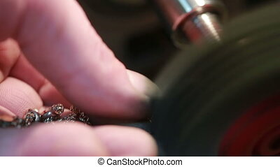 jeweler polishes gold chain. repair of jewelry