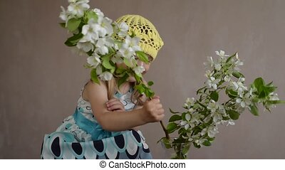 Girl playing with a blooming apple twig - Little girl...