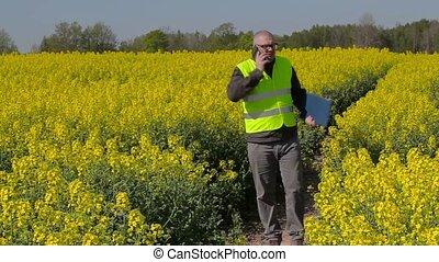 Farmer talking on smart phone and walking on rape field