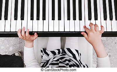 Child playing piano - Closeup of childs hands playing the...