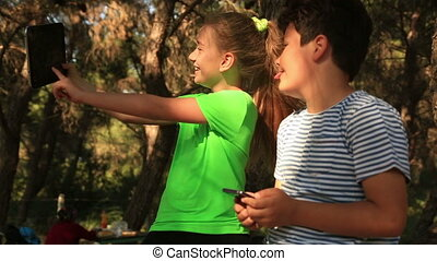 Young girl and boy taking a selfie - Closeup outdoor...