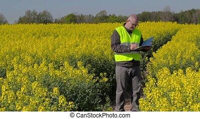 Farmer writing and walking on rape field
