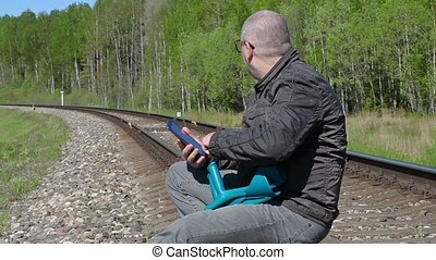 Disabled man with crutches sitting on railway and using...