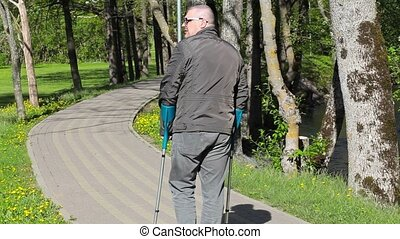 Disabled man with crutches walking away on path
